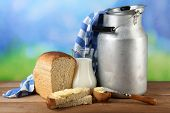 foto of milk products  - Retro can for milk with fresh bread and jug of milk on wooden table - JPG