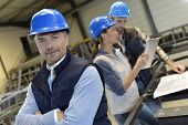 image of employee  - Supervisor in factory with employees in background - JPG