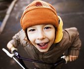 stock photo of little boys only  - little cute boy on bicycle smiling close up in hat - JPG