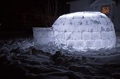 foto of igloo  - Homemade igloo lit up at night in the snow - JPG
