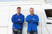 pic of handyman  - Smiling handymen looking at camera in front of their van - JPG
