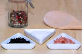 foto of peppercorns  - Three types of salt with colored peppercorns and cooking spoon - JPG