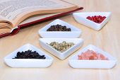 image of peppercorns  - Variety of peppercorns and salt with open cook book in background - JPG