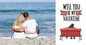 stock photo of couple sitting beach  - Affectionate couple sitting on the sand at the beach against cute valentines message - JPG