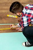 foto of laminate  - Carpenter worker installing laminate flooring in the room - JPG