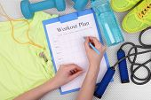 picture of gym workout  - Sports trainer amounts to workout plan close - JPG