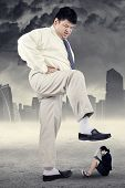 stock photo of stomp  - Business competition concept with little female entrepreneur trampled by big businessman - JPG