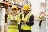 stock photo of warehouse  - Warehouse manager talking with worker in a large warehouse - JPG
