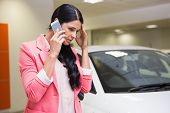picture of showrooms  - Sad woman calling someone with her mobile phone at new car showroom - JPG