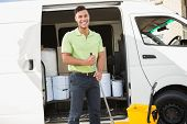 stock photo of cleaning agents  - Cleaning agent standing smiling at camera in front of his van - JPG