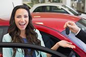 stock photo of excite  - Excited woman receiving car key at new car showroom - JPG