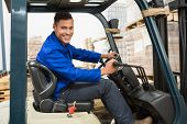foto of forklift driver  - Portrait of driver operating forklift machine in warehouse - JPG