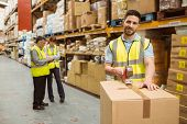 stock photo of warehouse  - Smiling warehouse workers preparing a shipment in a large warehouse - JPG