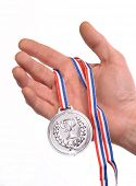 picture of medal  - Award winner hand holding a silver medal isolated on white background - JPG