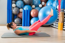image of pilates  - Ab exercise woman swiss ball leg lifts Pilates workout abs at gym - JPG