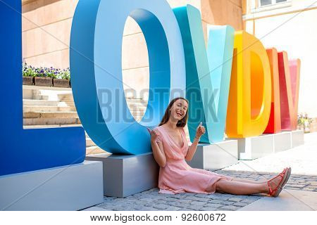 Woman sitting near the colorful letters