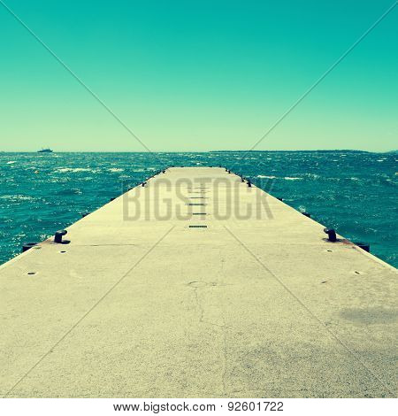 picture of a concrete dock with some mooring bollards in the Mediterranean sea, with a retro effect