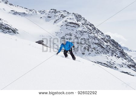 Man Snowboarding On Ski Holiday In Mountains
