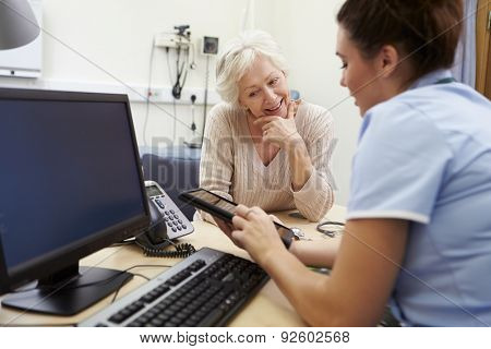 Nurse Showing Patient Test Results On Digital Tablet