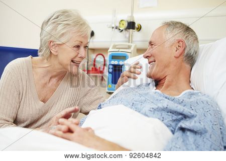 Senior Female Visiting Husband In Hospital Bed