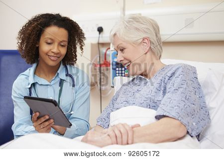 Doctor Sitting By Female Patient's Bed Using Digital Tablet