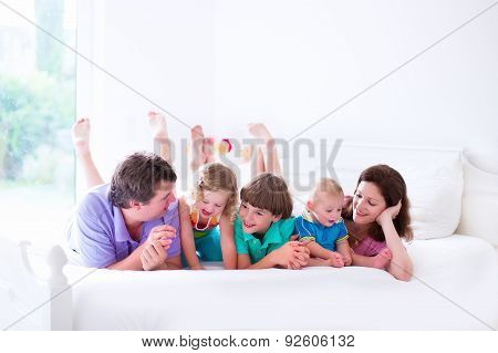 Family With Three Kids In Bedroom