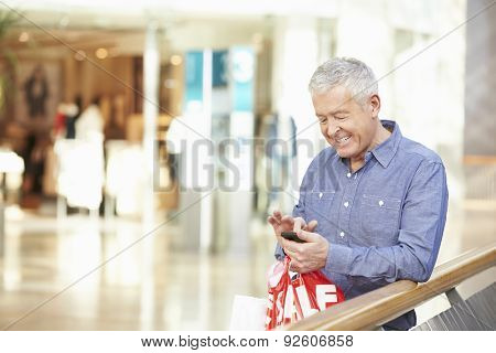 Senior Man In Shopping Mall Using Mobile Phone