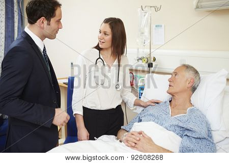 Medical Staff On Rounds Examining Senior Male Patient