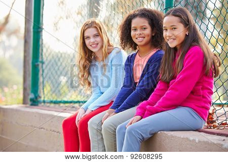 Three Young Girls Hanging Out Together In Park