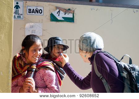 CUSCO, PERU - CIRCA MAY 2014: Tourist feeding a cute girl in a small village of Cusco, Peru.