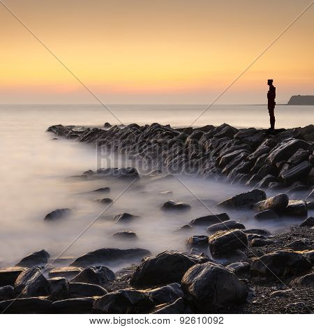 Lone Figure Stands Looking Out To Sea