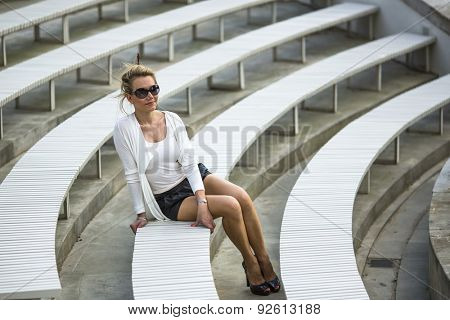 Attractive young woman on a bench in the amphitheater in the Park.