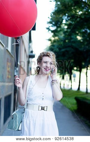 Curly Blond Girl With Big Red Ballon On The Phone