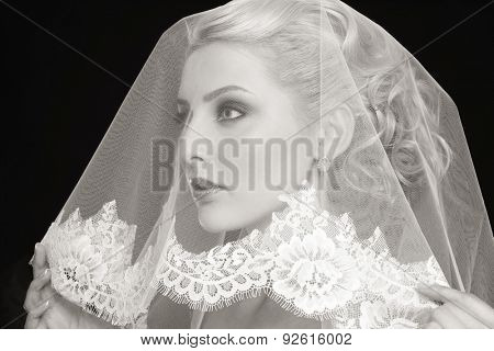 Duotone portrait of young beautiful blonde bride with bridal veil over her face