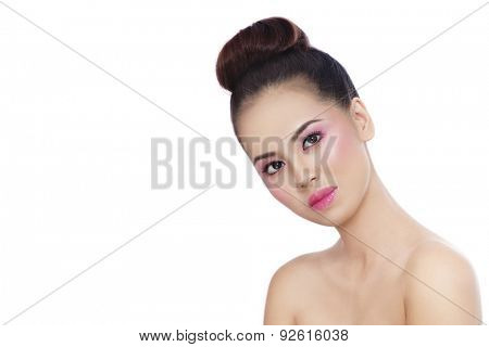 Young beautiful healthy asian girl with shiny pink makeup and hair bun over white background, copy space