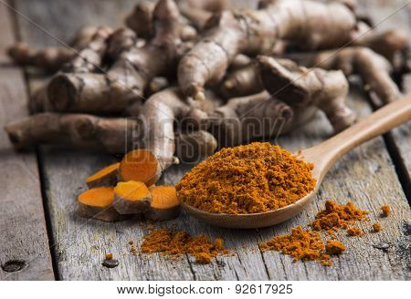 Pile Of Fresh Turmeric Roots On Wooden Table