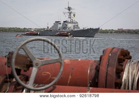 STATEN ISLAND, NY - MAY 20 2015: USS Barry (DDG 52) is guided into port by McAllister tugboats at Sullivans Pier, with red pipes in the foreground, at the beginning of Fleet Week.