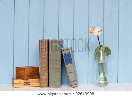 Books Pile, Two Wooden Boxes And White Rose In The Bottle