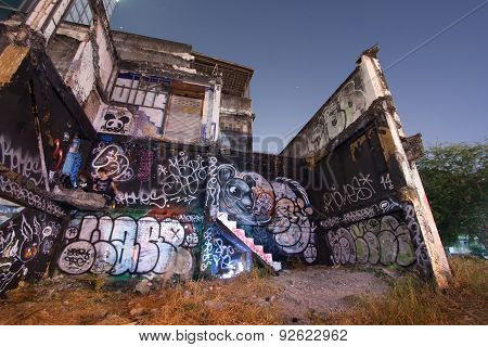 Unknown Graffiti Artist Painting On Abandoned Building Wall