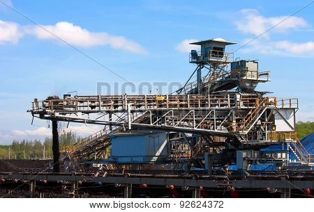 Large Conveyor Belt Carrying Coal And Emptying Onto A Huge Pile.