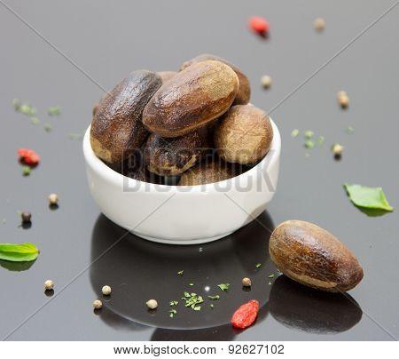 Whole Nutmegs  On Black Background.