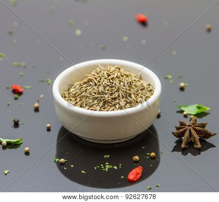 Cumin Seeds In The Bowl  On Black Background.