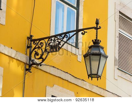 Black Wrought Iron Wall Lantern On A Yellow Wall.