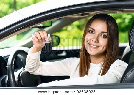 Pretty girl sitting inside car and holding key