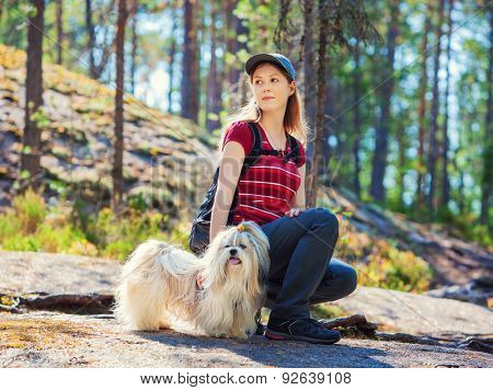Young woman tourist sitting on stone with dog in summer forest.
