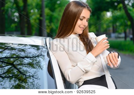 Lady standing near car and checking time