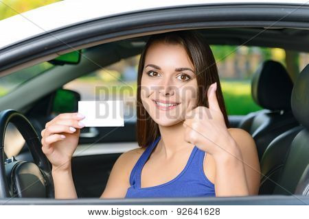 Attractive woman inside car showing card