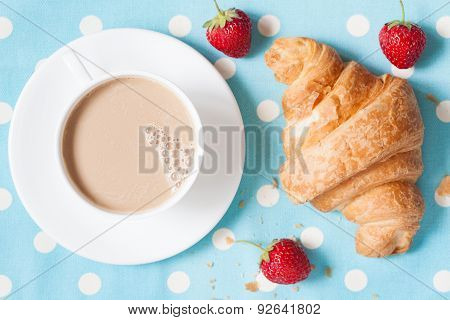 Traditional rustic croissant sweet French pastry and a cup of coffee latte with fresh strawberries o