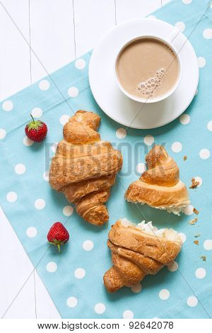Two croissants traditional french pastry sweet dessert with a cup of coffee latte and fresh strawber