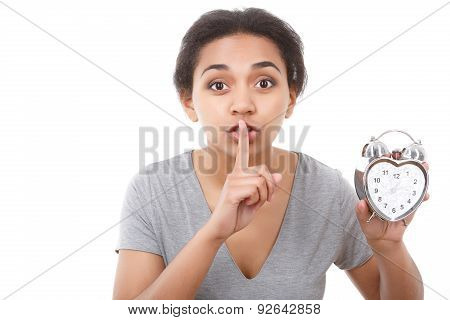 Young mulatto girl posing with alarm clock
